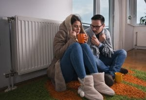 heater repair service heater repair service - Couple sitting beside radiator 300x207 - 9 Signs You Need to Call a Heater Repair Service