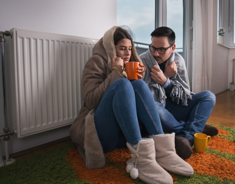heater repair service heater repair service - Couple sitting beside radiator 960x750 - 9 Signs You Need to Call a Heater Repair Service